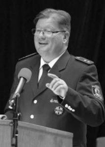 Klaus Dalferth an einem Rednerpult, er lächelt und hat den linken Zeigefinger erhoben